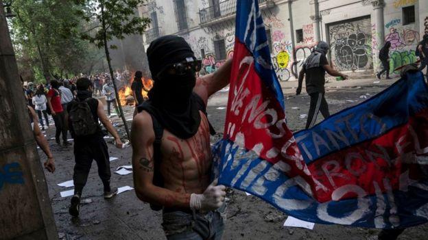 Hombre encapuchado levanta una bandera reivindicativa.