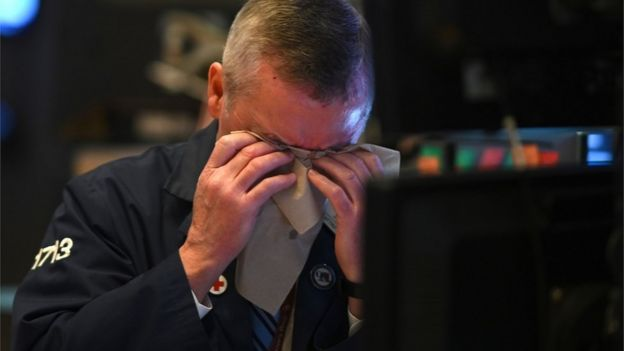 A trader wipes his brow on the NYSE floor