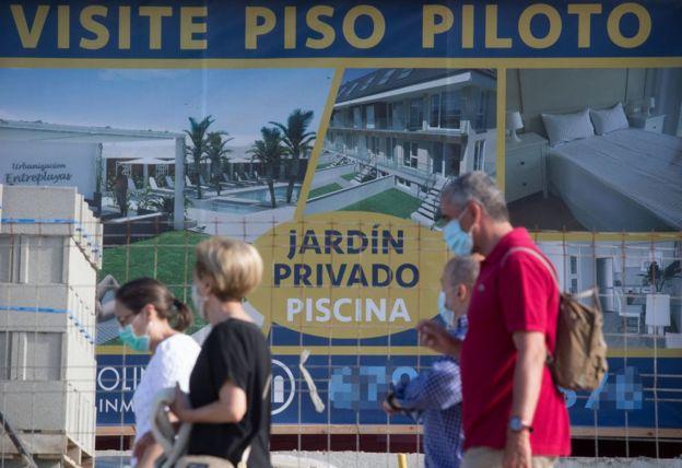 Un grupo de personas pasa frente al anuncio de unos apartamentos en A Mariña, Lugo, España, el 26 de julio de 2020.