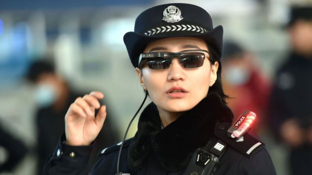 Image shows a police officer wearing a pair of sunglasses with a facial recognition system at Zhengzhou East Railway Station in Zhengzhou in China's central Henan province.