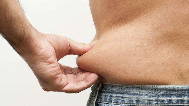 Hombre cogiéndose parte del abdomen.