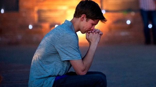 Spencer Greenlee, a student at Columbine High School, sits in prayer at the memorial