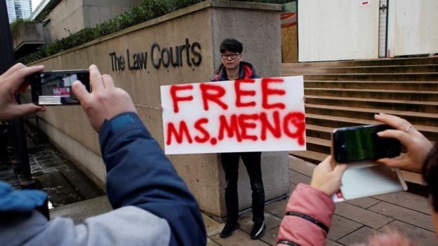 """Un hombre con un letrero que dice """"Liberen a Meng""""."""