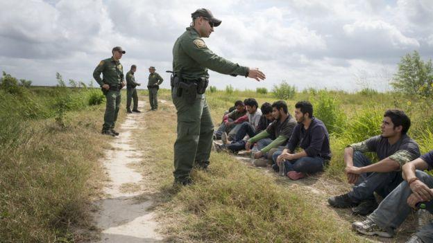 Agentes ante migrantes detenidos