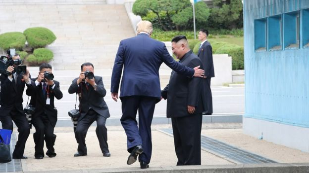 US President Donald Trump steps into North Korea next to Kim Jong-un (30 June 2019)