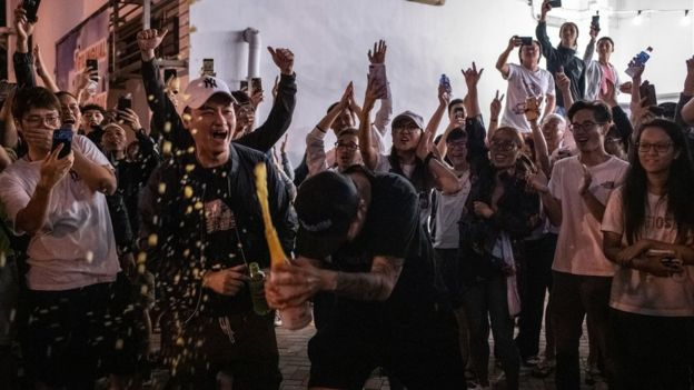 Pro-democracy campaigners celebrate pro-Beijing candidate Junius Ho losing his seat in local elections (25 Nov 2019)