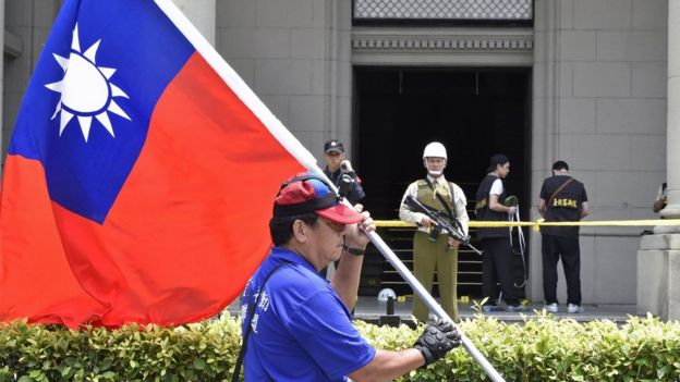 A pro-unification activist displays a Republic of China flag near the roped-off rear entrance to the Presidential Palace complex, where a samurai sword-wielding attacker slashed a police guard, in Taipei on August 18, 2017.