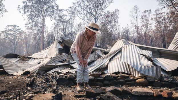 Ms Plesman stands on top of the remains of her home following a wildfire