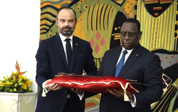 Le président sénégalais Macky Sall (à droite) reçoit l'épée d'El Hadj Omar Tall lors d'une cérémonie avec le Premier ministre français Edouard Philippe au Palais de la République à Dakar, Sénégal, le 17 novembre 2019.