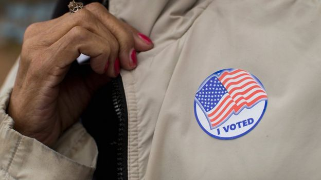 A Voter Shows Off Her I Voted Sticker As She Leaves A Polling Place