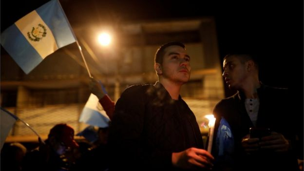 Hombres con velas y banderas en una vigilia en apoyo a la Cicig.