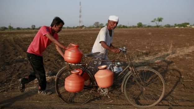 Residents push a bicycle loaded with water containers through a field in Latur
