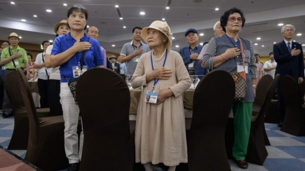 Elderly South Koreans and assistants stand for the national anthem at a briefing in a hotel (19 Aug 2018)