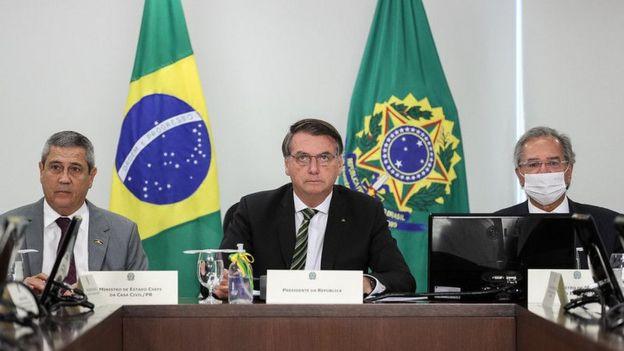 Braga Netto, Bolsonaro e Guedes sentado em mesa de reunião, com feições sérias e bandeiras no plano de fundo
