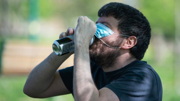 Man lifts a face mask to swig lager from a can