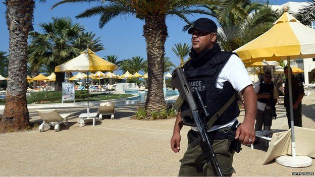 A Tunisian security member stands next to a swimming pool at the resort town of Sousse 26 June 2015