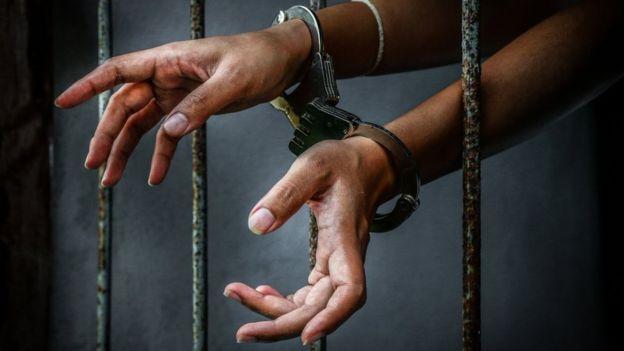 Руки в наручниках за тюремной решеткой