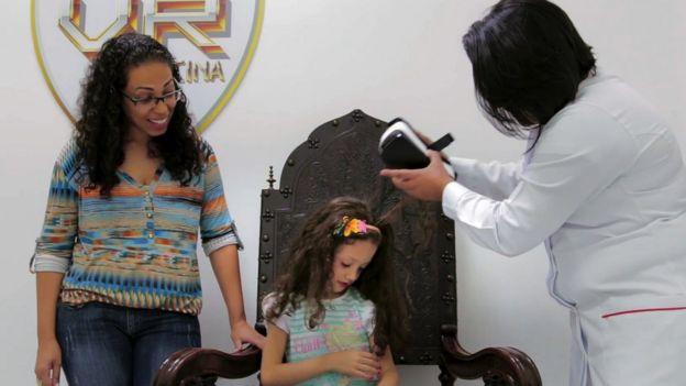 Enfermeira tira o headset de realidade virtual de uma menina, enquanto sua mãe observa a cena