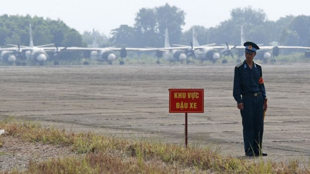 Vietnamese soldier stands next to a hazardous warning sign by a runway at Bien Hoa air base