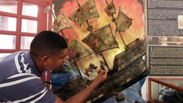Homem observa réplica de navio