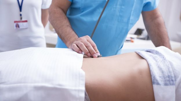 Mulher sendo atendida por médico