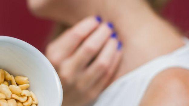 Mulher coçando pescoço e pote de amendoim em primeiro plano