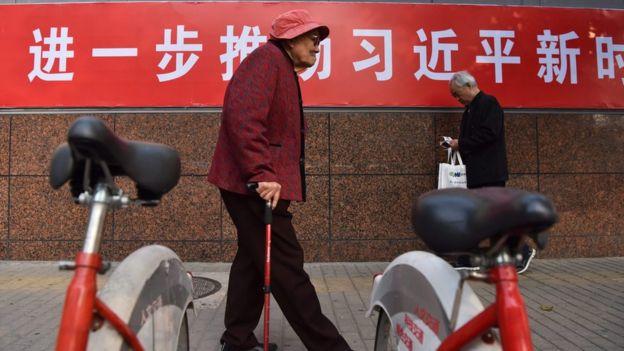 北京市民走在宣传习思想的标语旁。