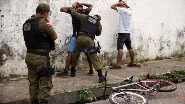 Policiais militares revistam homens nas ruas de Belém, Pará