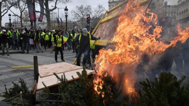 Manifestantes quemando árboles de navidad