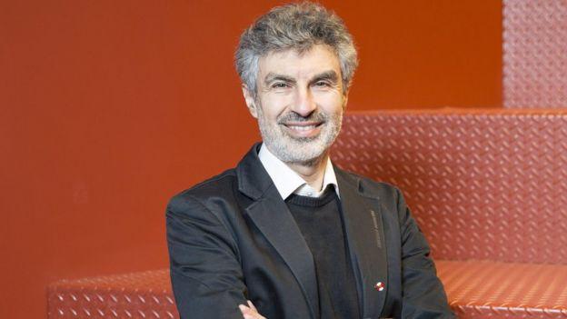 O pesquisador Yoshua Bengio posa sorrindo em frente a um fundo vermelho