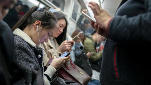 Chineses olham para seus celulares no metrô