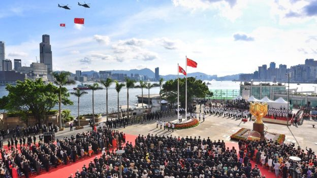 The China and Hong Kong flags are flown past by helicopters during a ceremony at Golden Bauhinia Square in Hong Kong, 1 July 2017