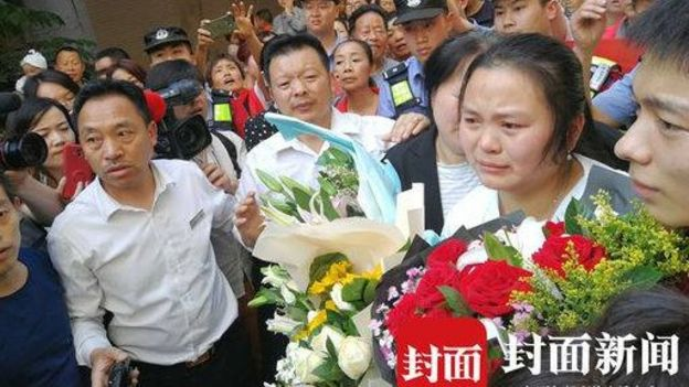 Kang Ying holding flowers, surrounded by her family