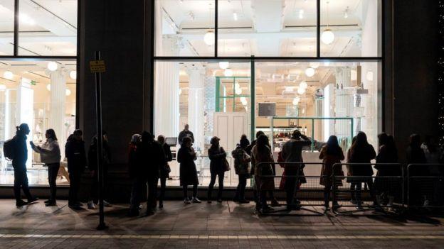 People queue in the dark