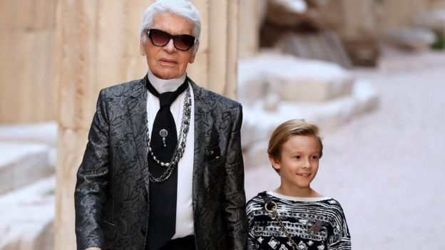 In this file photo taken on May 3, 2017 German fashion designer Karl Lagerfeld acknowledges the audience with his godson Hudson Kroenig at the end of his Chanel Croisiere (Cruise) fashion show at the Grand Palais in Paris