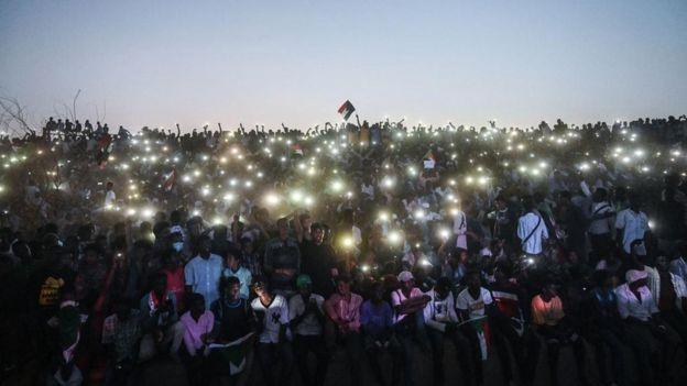 Pessoas com celulares erguidos em protesto no Sudão