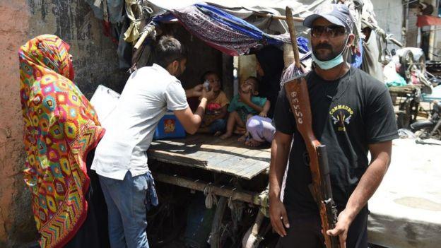 عاملون صحيون يعطون الأطفال تطعيما ضد شلل الأطفال في حماية مسلحين