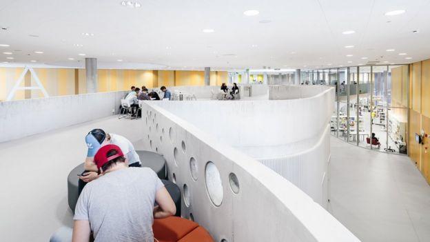 Estudiantes trabajan en un espacio abierto en una escuela finlandesa, con mobiliario ajustable.