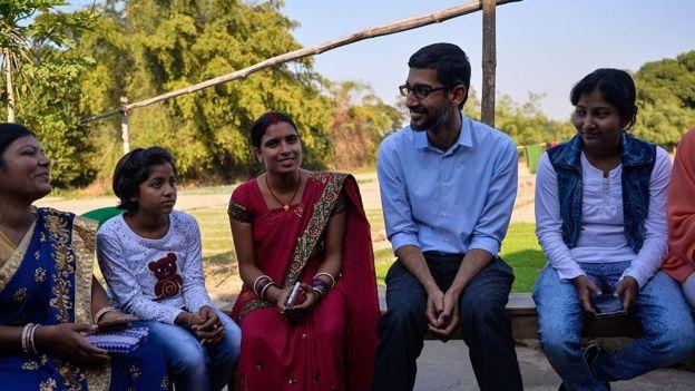 Sundar Pichai na Índia, ao lado de mulheres e criança, em 2017