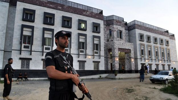 Pakistani policemen stand guard outside the hostel at Abdul Wali Khan university where students beat to death a classmate in Mardan on April 13, 2017.