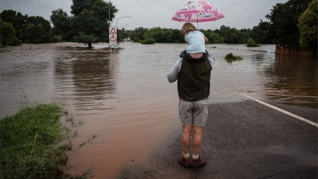 A man with his daughter look out over a flooded area in Centurion, Pretoria, South Africa, 09 December 2019