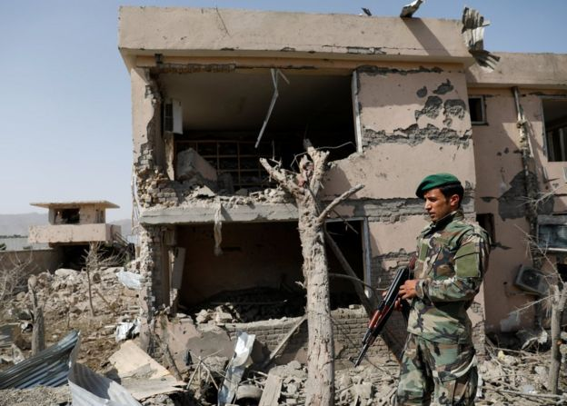 Afghan National Army officer inspecting a building that has been destroyed in the explosion