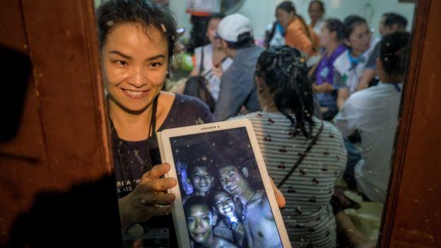 Una mujer sostiene una tablet con la foto de niños atrapados en Tailandia