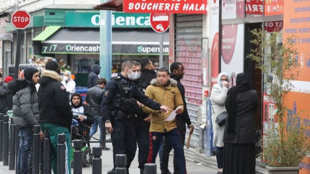 Policiais controlam pessoas de máscara em Saint Denis