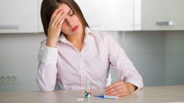 Mujer con dolor de cabeza frente a un frasco de pastillas