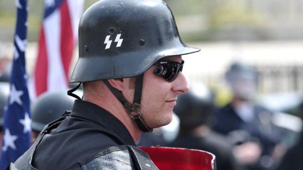 Homem usando capacete com símbolos nazistas