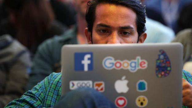 Hombre mirando una computadora portátil
