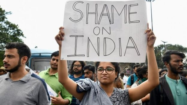 Students and activists hold placards during a protest in Bangalore