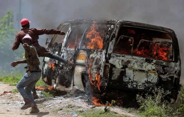 Supporters of the Kenyan opposition gesture near a burning vehicle in Embakasi, on the outskirts of Nairobi, Kenya, 28 November