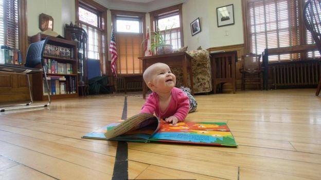 طفل رضيع يصوره أهله بجوار الخط الحدودي في مكتبة هاسكل